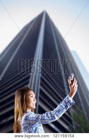 Smiling asian woman taking picture with camera against skyscraper