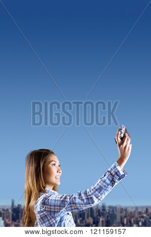 Smiling asian woman taking picture with camera against cityscape