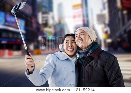 Smiling couple taking selfie against blurry new york street