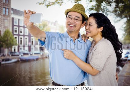 Man and woman taking a picture against canal in amsterdam