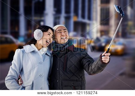 Couples taking funny pictures using smartphone against blurry new york street
