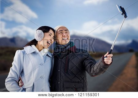 Couples taking funny pictures using smartphone against high angle view of road by mountains