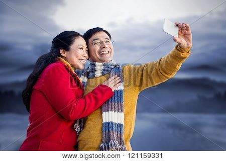 Older asian couple on balcony taking selfie against road leading out to the horizon at night