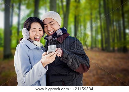 Cheerful couple looking at the smart phone against tree trunks in the forest