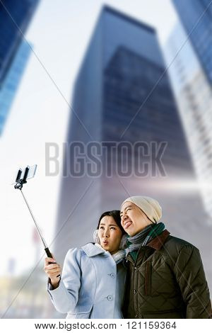 Playful couple taking selfie against building against skyscraper in city