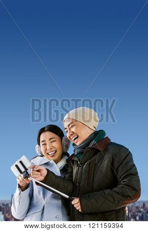 Couple laughing at their pictures taken on smartphone against cityscape