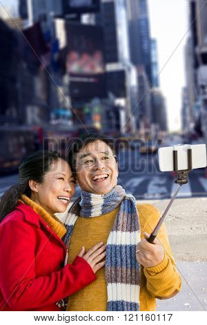 Older asian couple on balcony taking selfie against picture of a city