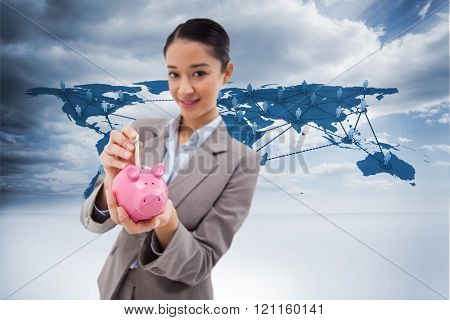 Portrait of a businesswoman putting a bank note in a piggy bank against view of a global map