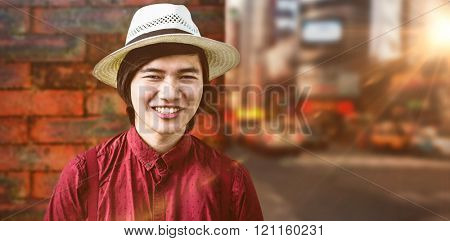 Smiling hipster with a straw hat against wall of a house