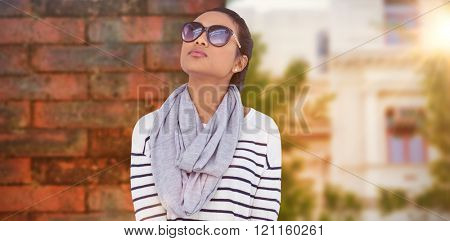 Asian woman with luggage looking up against wall of a house