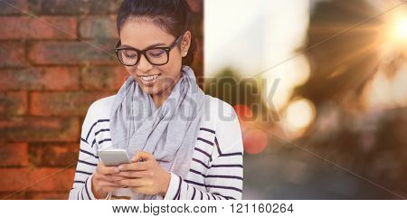 Smiling Asian woman using smartphone against wall of a house