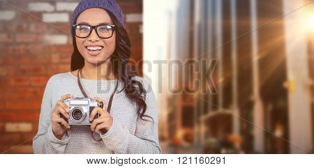 Asian woman holding digital camera against wall of a house