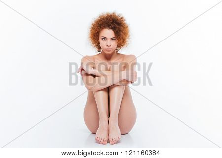 Nude woman with curly hair sitting on the floor isolated on a white background and looking at camera