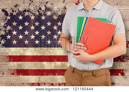 Mid section of man holding files against usa flag in grunge effect