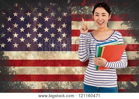 Cheerful woman pointing up while holding files against usa flag in grunge effect