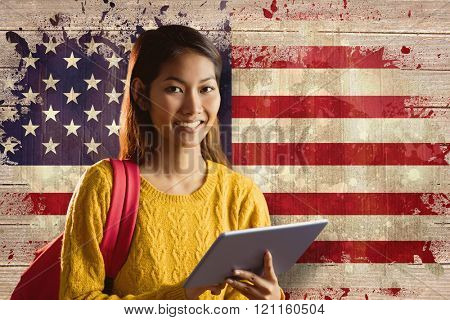 Smiling asian female student using tablet against usa flag in grunge effect
