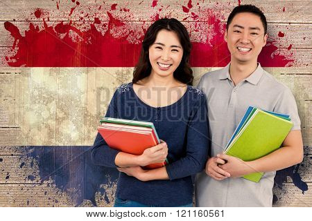 Happy couple holding books against netherlands flag in grunge effect