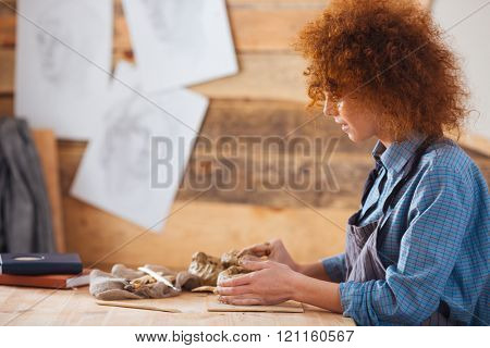 Profile of focused redhead young woman ceramist creating sculpture using clay in pottery workshop