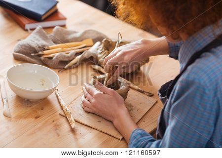 Concentrated curly young woman working on clay pot sitting in art studio