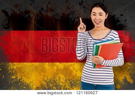 Cheerful woman pointing up while holding files against germany flag in grunge effect