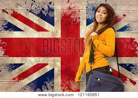 Female college student with bag in park against union jack flag in grunge effect