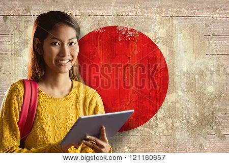 Smiling asian female student using tablet against japan flag in grunge effect
