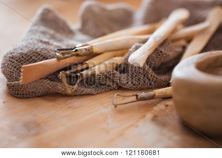 Set of dirty art and craft sculpting tools on wooden table in pottery workshop