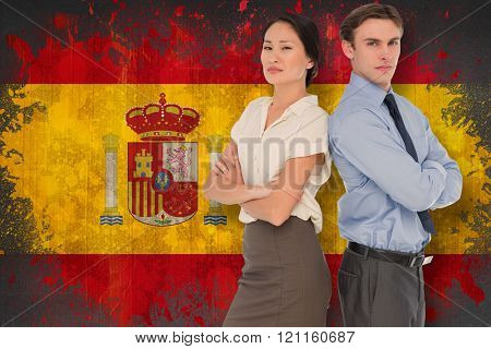 Business colleagues with arms crossed in office against spain flag in grunge effect