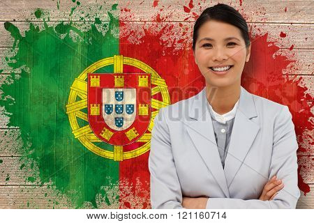 Smiling businesswoman with folded arms against portugal flag in grunge effect