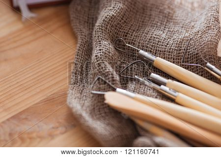 Closeup of set of craft sculpting tools for working with clay lying on wooden table