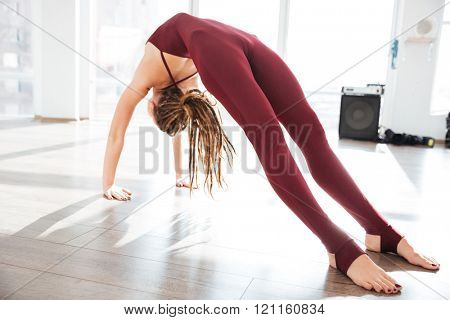 Attractive young woman bending and stretching on the floor in yoga studio