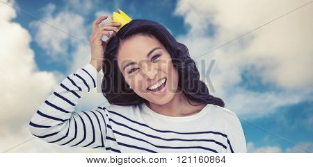 Smiling Asian woman with paper crown against road leading out to the horizon