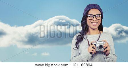 Asian woman holding digital camera against beautiful blue cloudy sky
