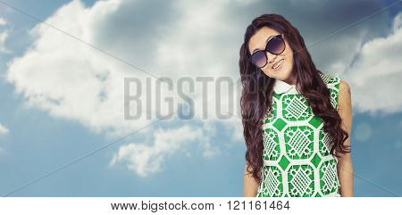 Asian woman with sunglasses posing for camera against beautiful blue cloudy sky