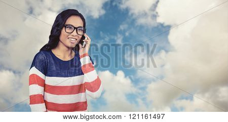 Asian woman on a phone call against blue sky with white clouds
