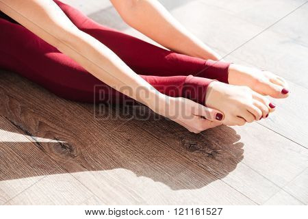 Closeup of slim legs of young woman gymnast sitting and stretching on wooden floor