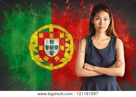 Businesswoman with crossed arms against portugal flag in grunge effect