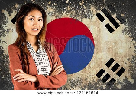 Smiling businesswoman with crossed arms against korea republic flag in grunge effect