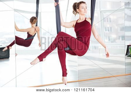 Attractive thoughtful young woman doing pose of aerial yoga using hammock