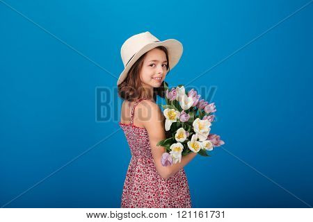 Back view of happy pretty little girl holding bouquet of flowers over blue background
