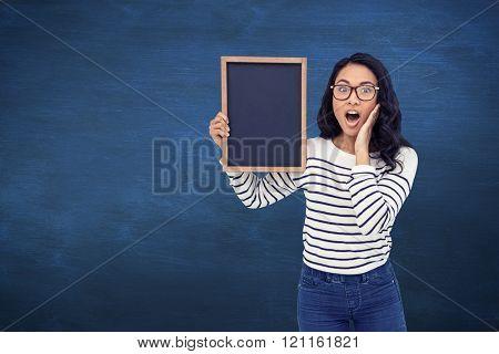 Surprised Asian woman holding blackboard against blue chalkboard