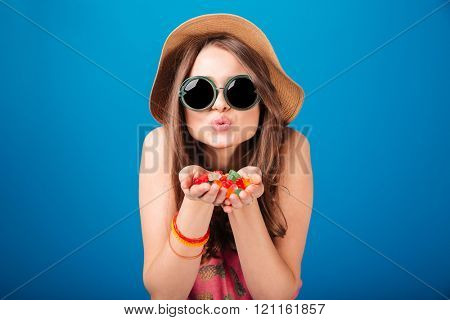 Cute lovely young woman holding jelly candies on palms and sending a kiss over blue background