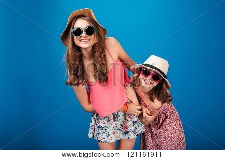 Two cheerful cute sisters in sunglasses and hats standing and having fun over blue background