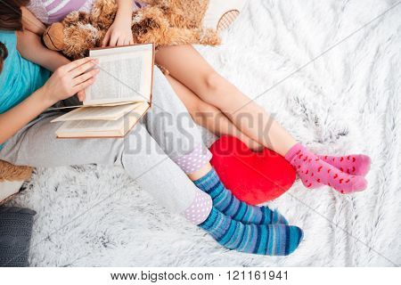 Closeup of beautiful legs of two young women sitting and reading a book on soft carpet