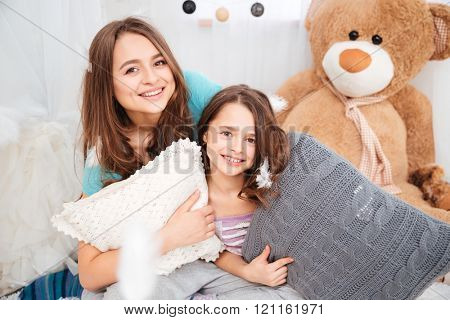 Portrait of two beautiful smiling sisters with pillows playing in children room