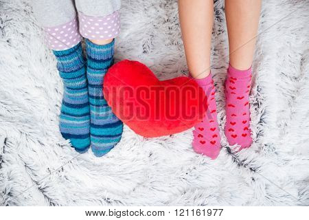 Closeup of slim beautiful legs of two young women in colorful socks on the carpet