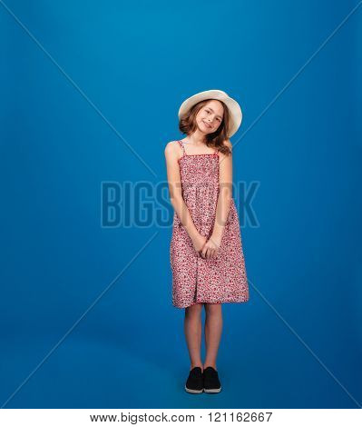 Full length of pretty cheerful little girl in sundress and hat standing and looking at camera over blue background
