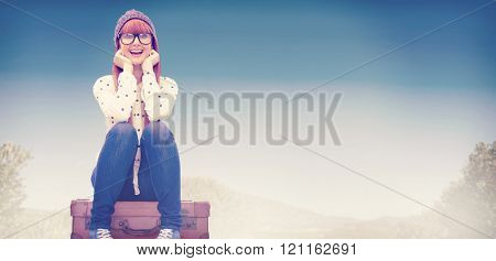 Smiling hipster woman sitting on suitcase against mountain trail