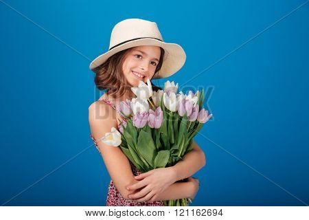 Cheerful pretty little girl in hat holding bouquet of flowers over blue background