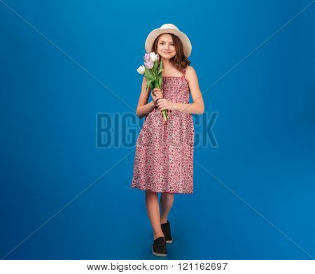 Full length of cute happy little girl in sundress and hat standing and holding bouquet of fresh tulips over blue background